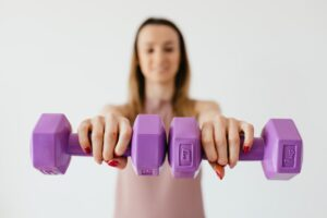 woman holding 2 purple dumbbells