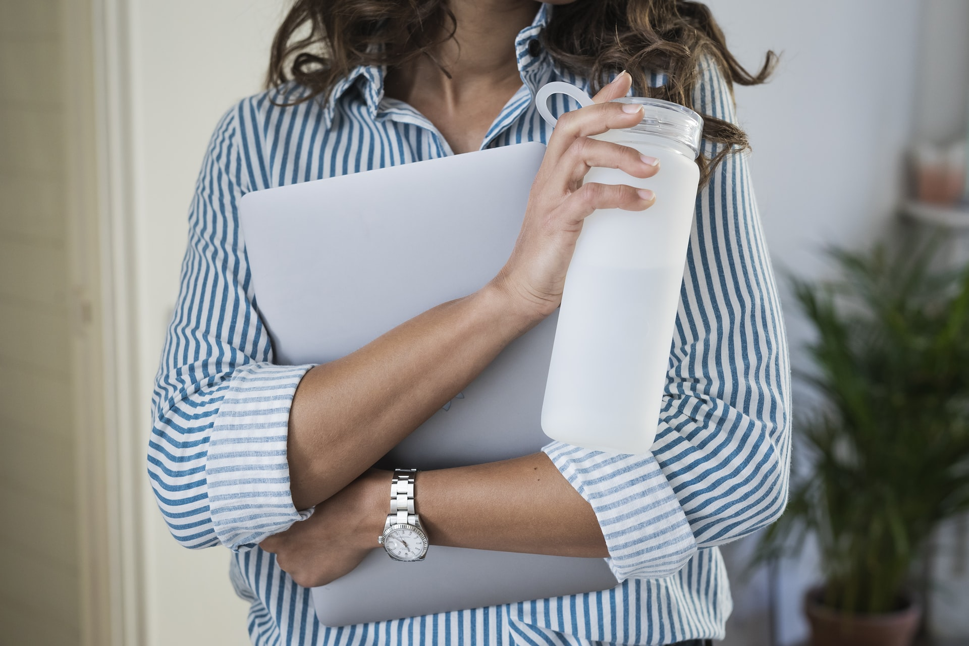 woman in white and blue shirt holding a white bottle and laptop