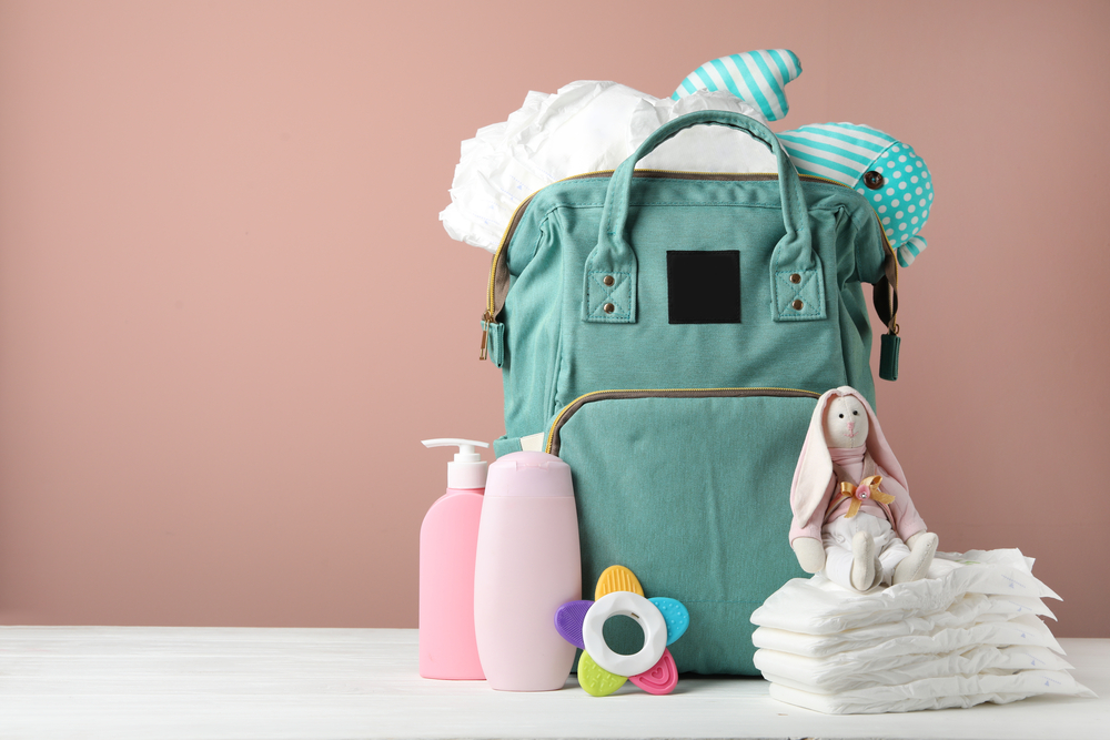 Bag with diapers and baby accessories on white wooden table