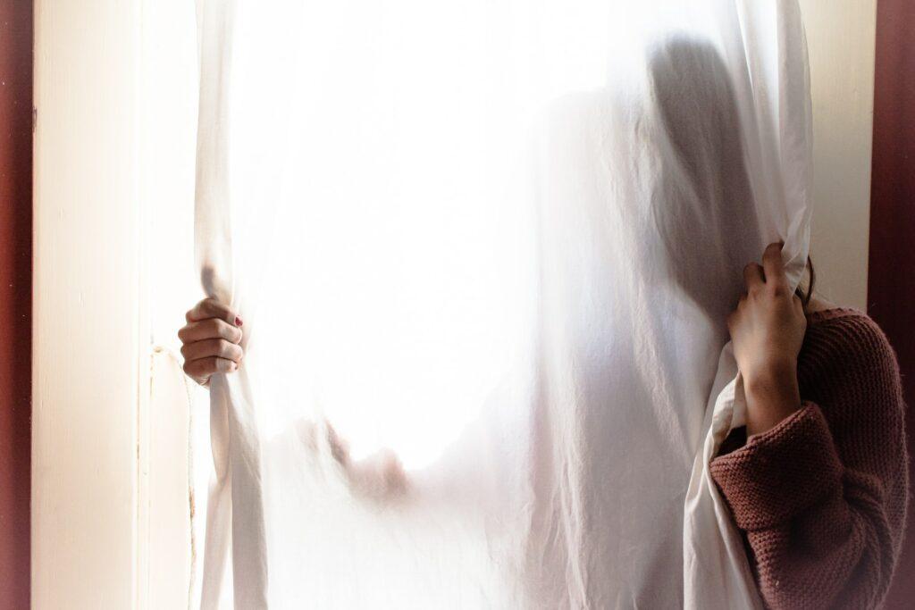 person hiding behind cutains