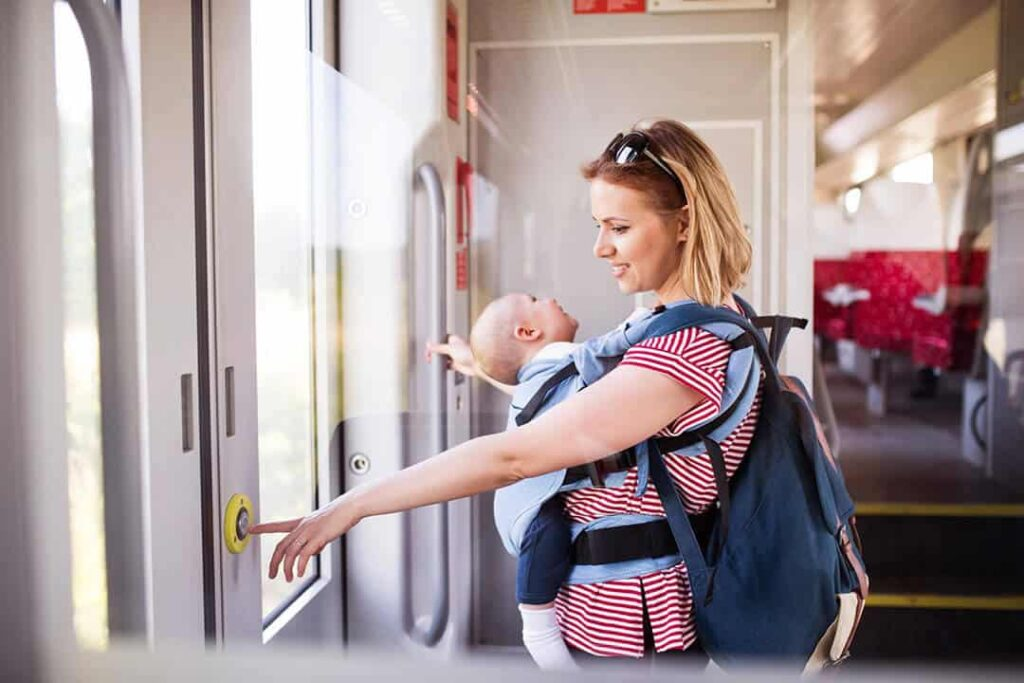 mother holding a baby and a diaper bag