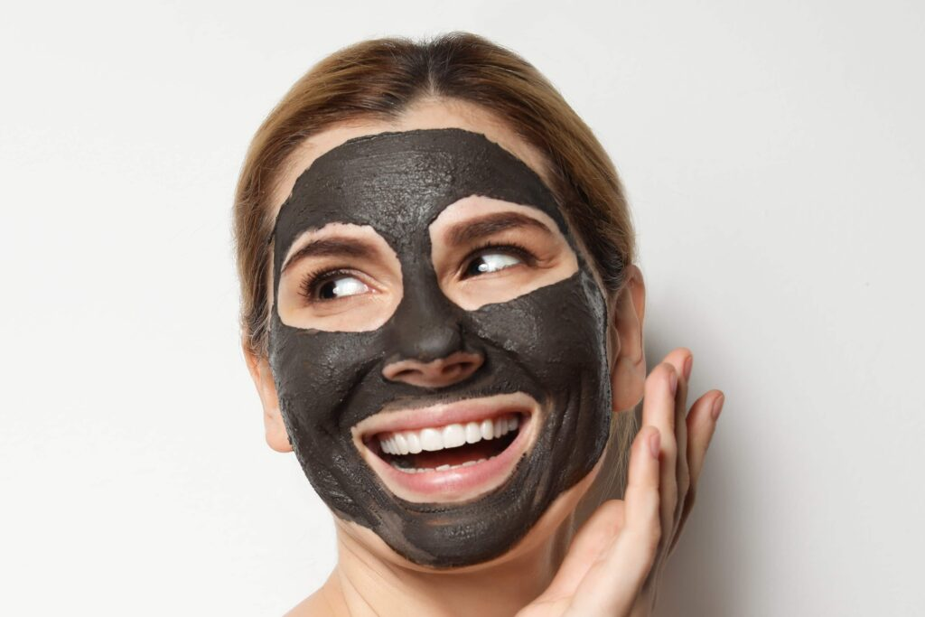 woman using charcoal mask
