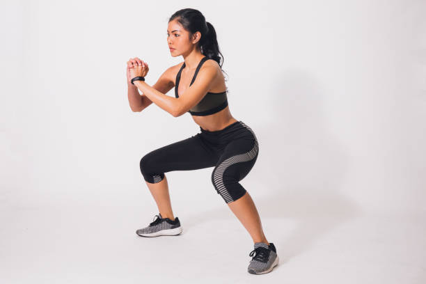 Young sporty muscular woman doing squats