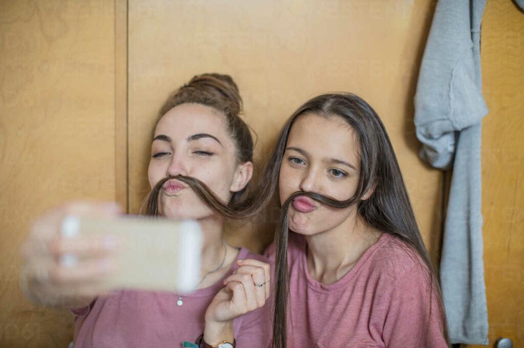 Playful happy teenage girls taking a selfiePlayful happy teenage girls taking a selfie