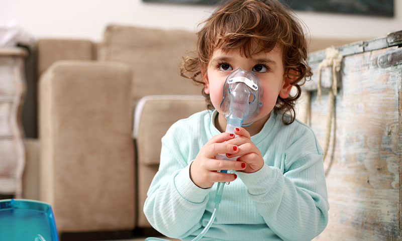 Little girl with asthma problems or allergy using inhaler
