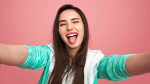 a girl sticking out her tongue while taking selfie