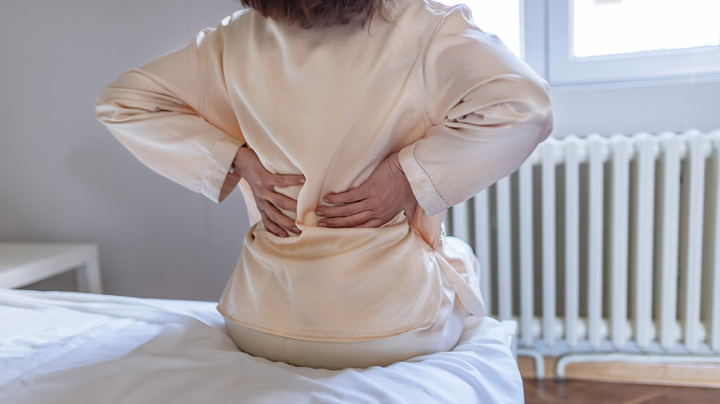 woman having lower back pain after waking up